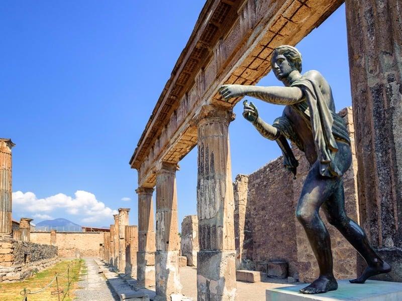 Ruins of the antique Temple of Apollo with bronze Apollo statue in Pompeii