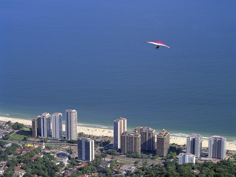 Hang glider flying over the Sao Conrado neighborhood after jumping the ramp located in Pedra Bonita