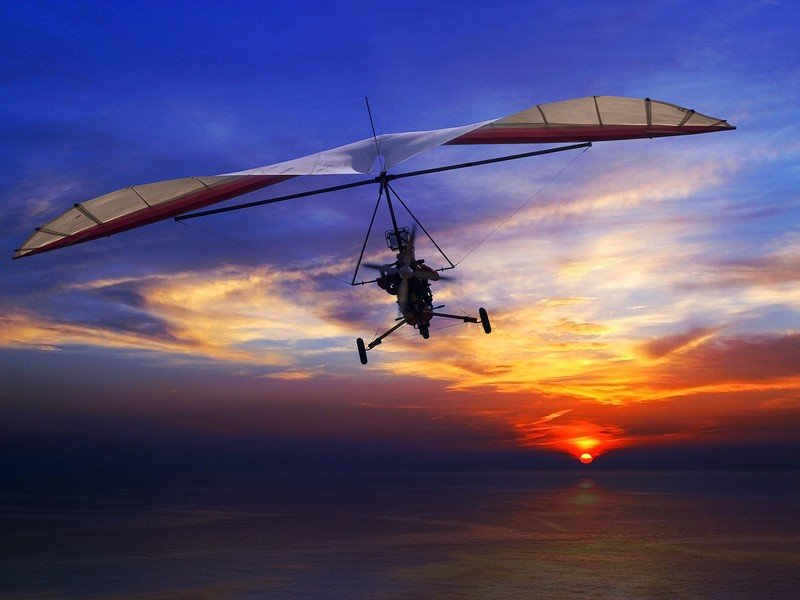Motorized hang glider in the sunset above sea