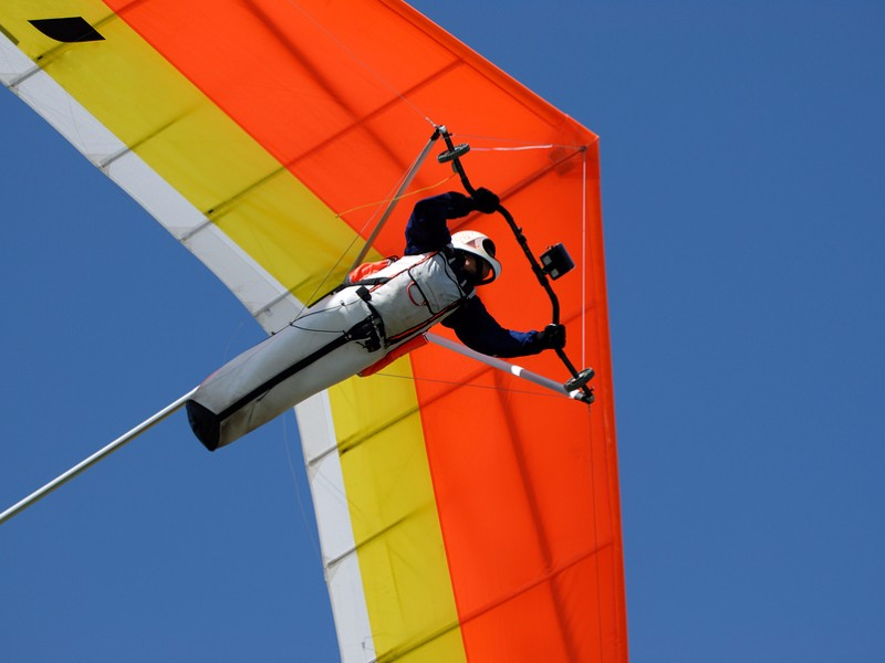 Yellow-red hang-glider under control in the sky