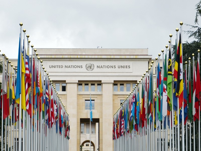 View of the entrance to United Nations (Palace of Nations) and world flags in Geneva