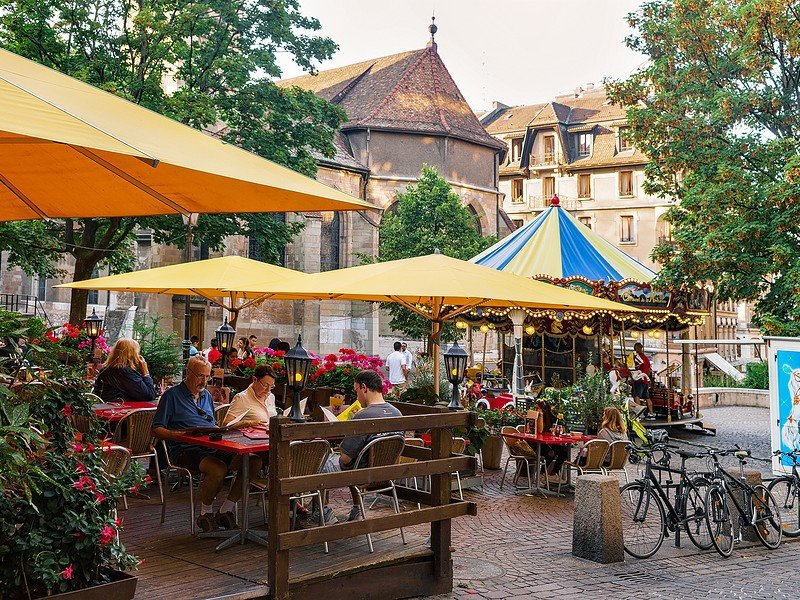 People in street open air restaurant at carousel and Madeleine Church in the old town in Geneva