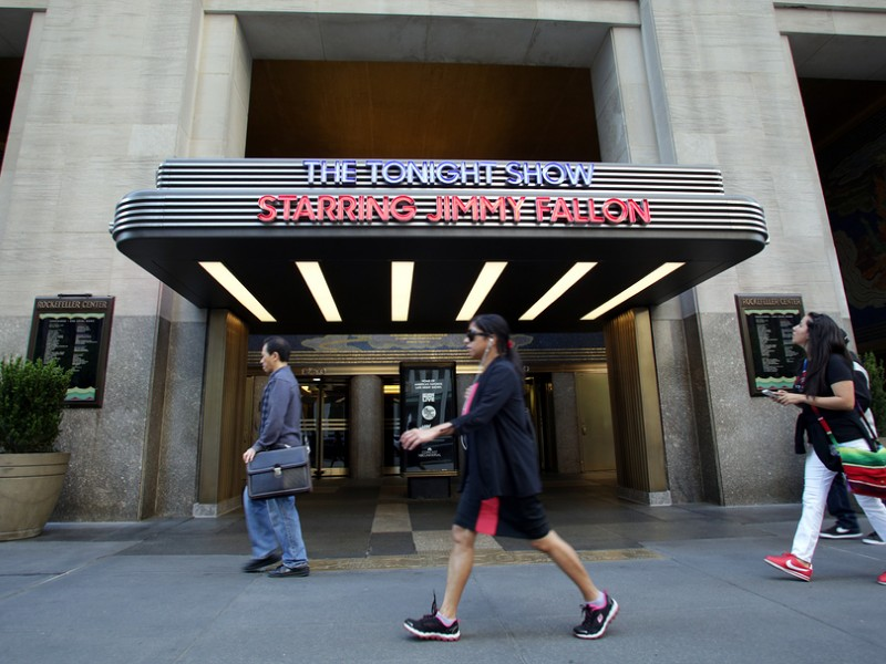 Pedestrians walk past the entrance to the NBC television studio hosting The Tonight Show with Jimmy Fallon