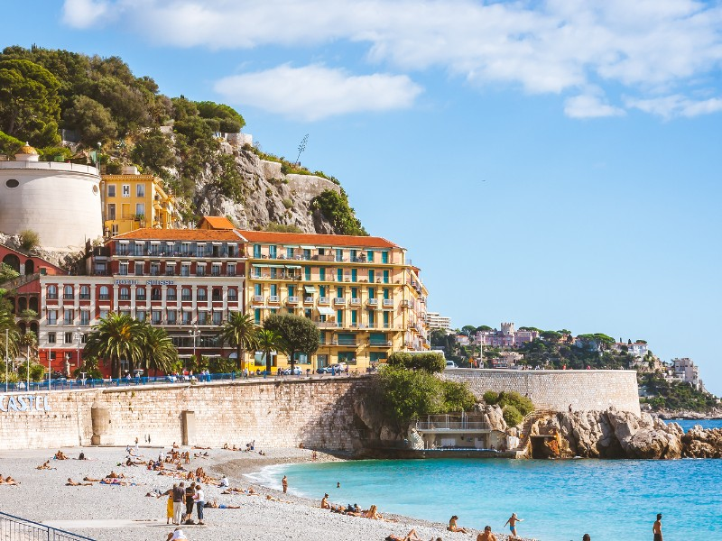 Beautiful architecture and people relaxing on beach that stretches along Promenade des Anglais in Nice