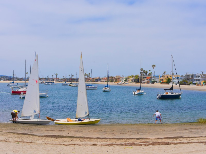Sailboats and people on the blue waters of Mission Bay in San Diego.
