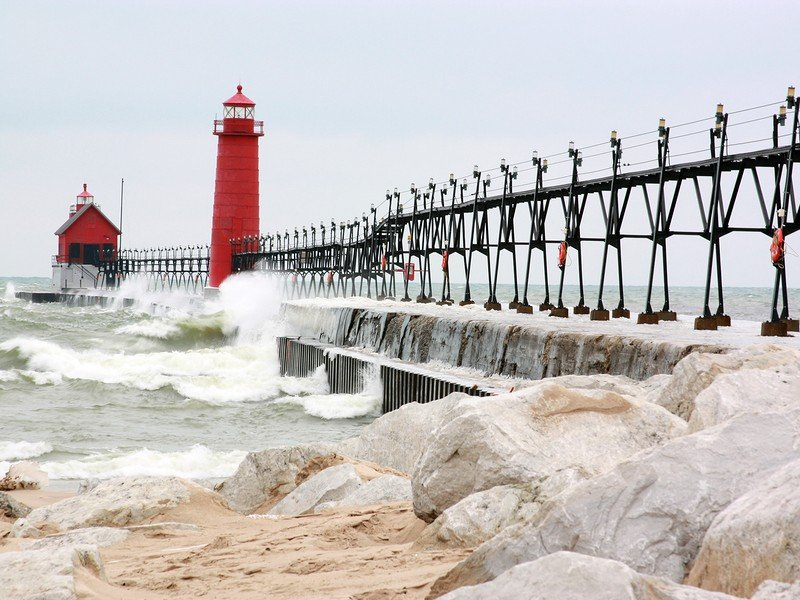 Beach rocks with a pier in the background in Grand Haven, MI