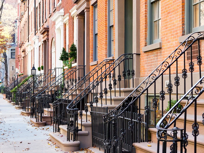 Row of old historic brownstone buildings along an empty sidewalk block in the Greenwich Village neighborhood of Manhattan New York City