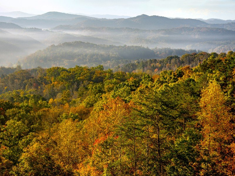 The sun rises over the mountains of Great Smoky Mountains National Park at the peak of autumn's colors