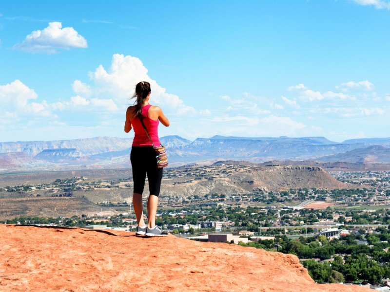 Woman atop the Sugarloaf rock formation overlooking St George, Utah