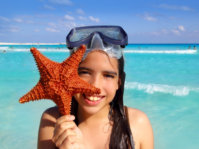 Girl holding starfish on the beach in Cancun, Mexico