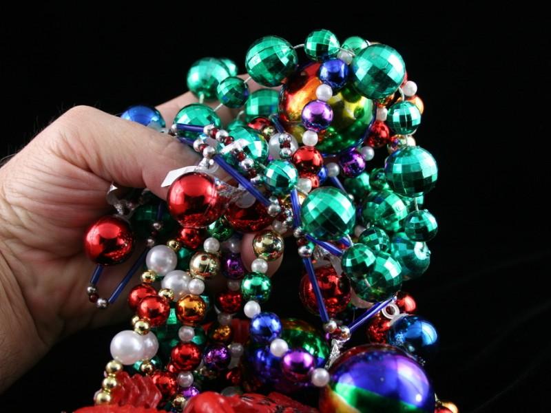 Hand holding Mardi Gras beads