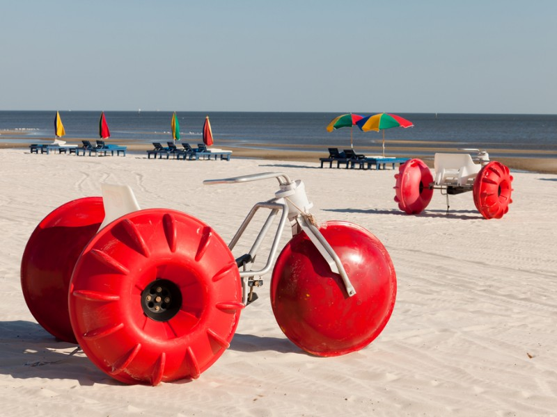 Colorful beach tricycles along the shoreline with lounge chairs and umbrellas along the Mississippi Gulf Coast