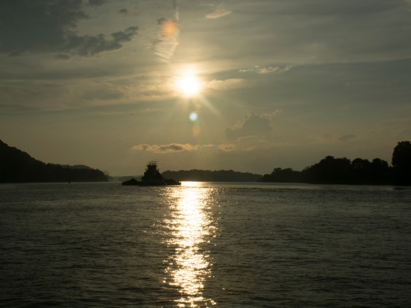The sun begins to set on the Ohio river at Parkersburg West Virginia with Blennerhassett Island in the distance