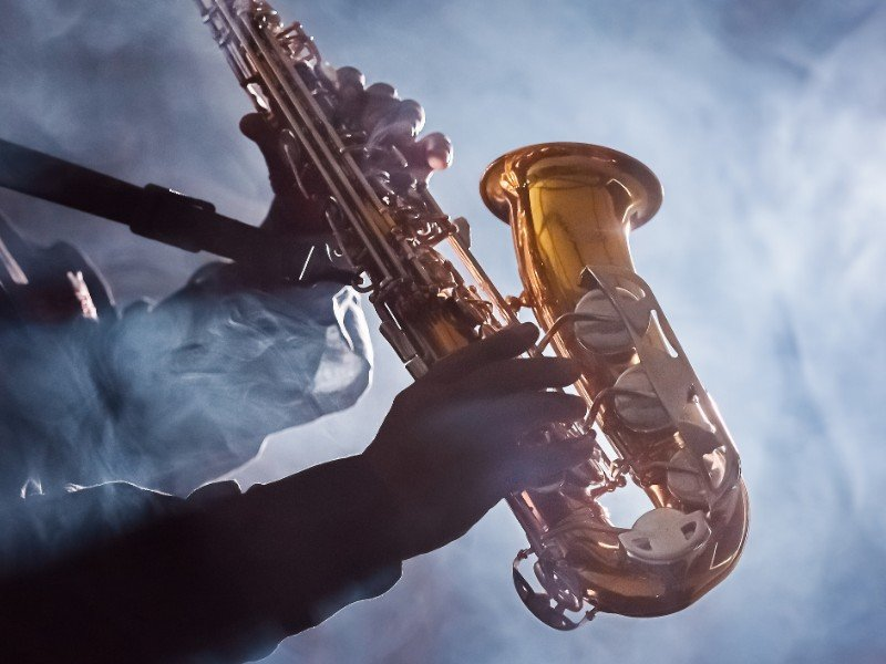 Jazz musician playing the saxophone in smokey club
