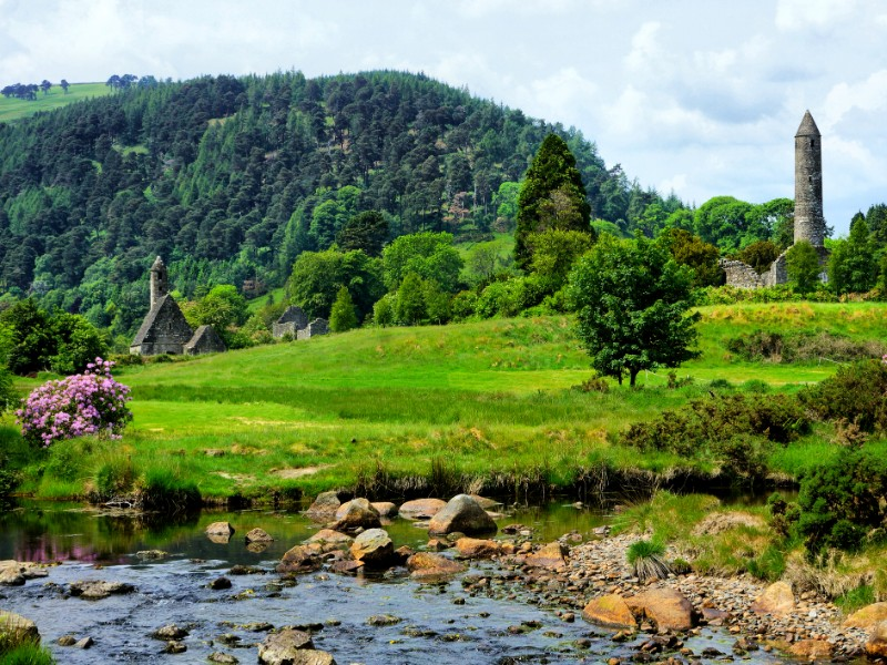 View of the historic Glendalough monastic site with ancient round tower and church in Wicklow National Park
