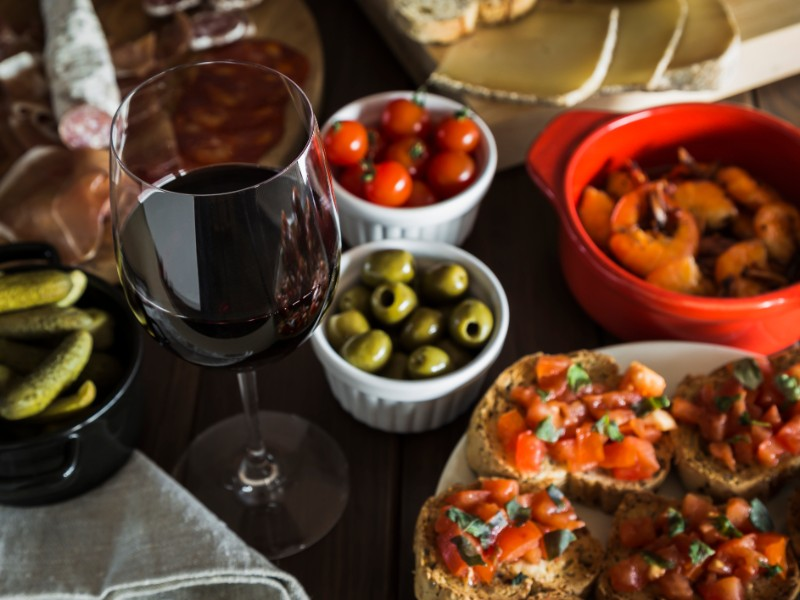 Red wine and tapas dishes on a wooden table