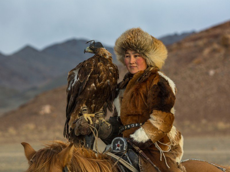 Golden Eagle Hunter teaches her young daughter in Western Mongolia