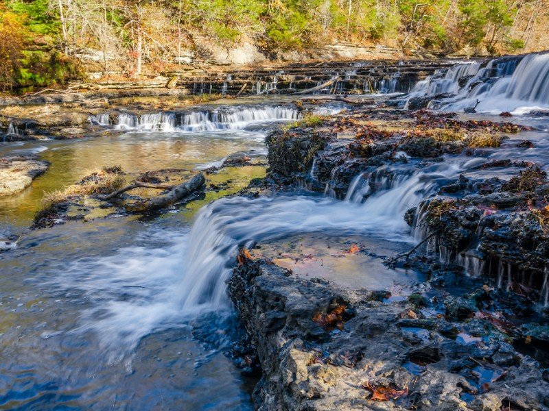 Clear water cascades over rock shelves at Burgess Falls State Park