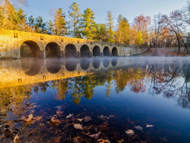 Fog and morning light on this fall scene on Byrd Lake Dam at Cumberland Mountain State Park