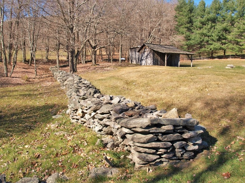 A rock wall surrounds the log cabins that were part of a homestead in Grayson Highlands State Park